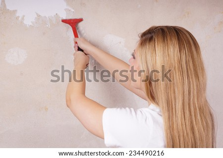 young woman is scraping off old wallpaper - stock photo