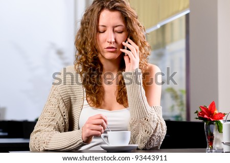 young woman is sitting at cafe and talking phone