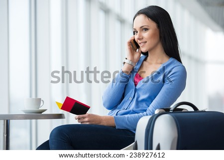Young woman is sitting in the airport with coffee while waiting for flight. She is speaking by phone. - stock photo