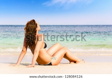 young woman is sitting on beach - stock photo