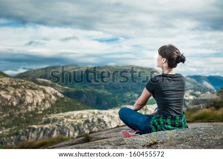 Young woman is sitting on cliff's edge and looking to a sky with clouds - stock photo