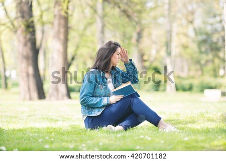 Young woman is sitting on the grass in a park and reading a book on a nice and sunny spring day. - stock photo