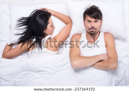 Young woman is sleeping in the bed. Husband is looking at camera.