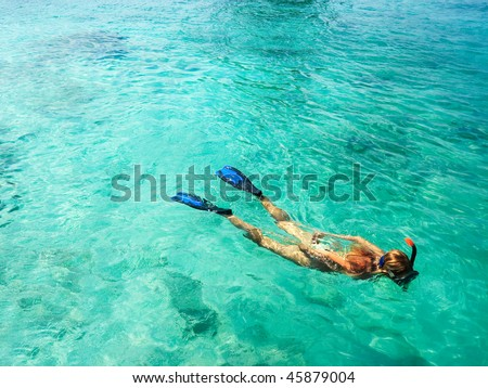 Young woman is snorkeling in tropical lagoon - stock photo