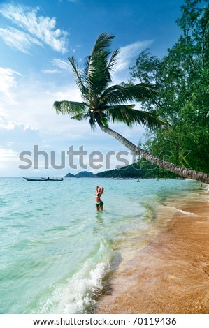 Young woman is standing in the sea under the palm tree - stock photo