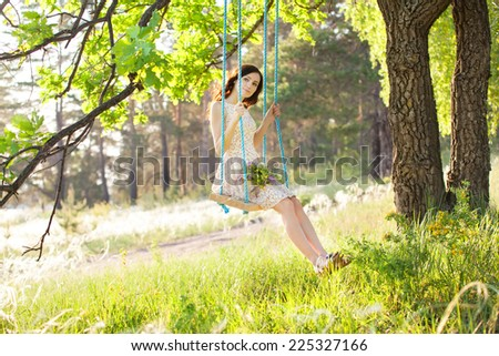Young woman is swinging on a swing in summer forest. - stock photo