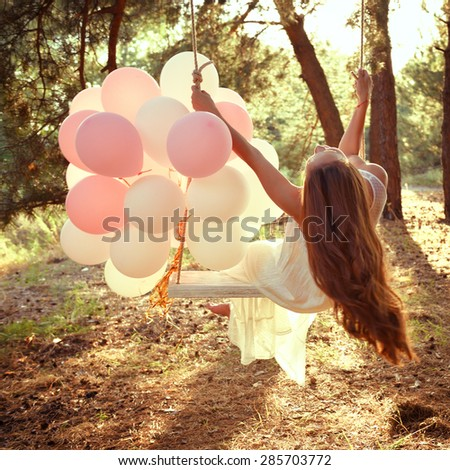 Young woman is swinging on a swing in summer pine forest. Image toned and noise added. - stock photo