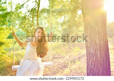 Young woman is swinging on a swing in summer pine forest. Image toned and noise added. High key. - stock photo