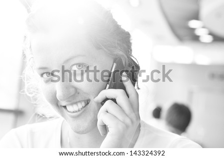 young woman is talking phone and looking at camera - stock photo