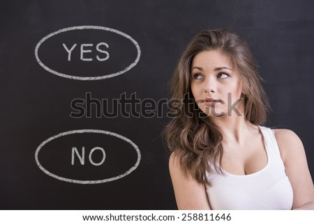 Young woman is thinking about yes or no in front of blackboard. - stock photo