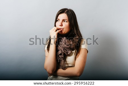 Young woman is thinking and nervous hand to her mouth. On a gray background. - stock photo