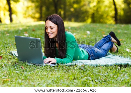 Young woman is using her laptop while lying down in the nature,Woman using laptop