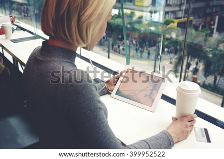 Young woman is watching movie in network on touch pad,while is sitting with take away coffee in cafe with city view outside window. Hipster girl is holding digital tablet with copy space on the screen - stock photo