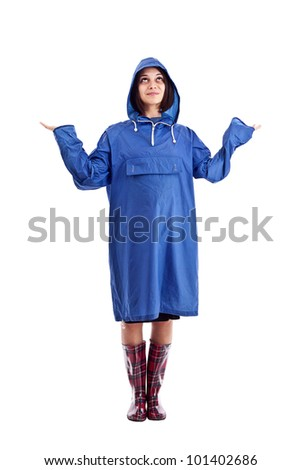 Young woman, isolated against a white background, wears a blue raincoat, waiting for it to rain. - stock photo