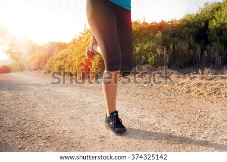 Young woman jogger tying hers shoes outdoors