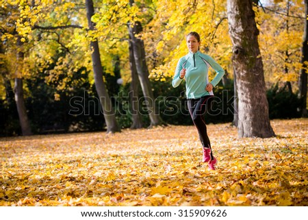 Young woman jogging and training in autumn nature - stock photo