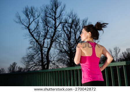 Young woman jogging at night with the tree in the background. Girl running outdoors in a city park. Color toned image. - stock photo
