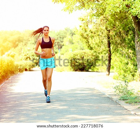 Young woman jogging at park - stock photo