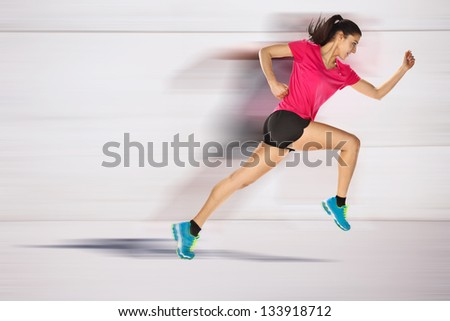 young woman jogging front cement wall. Sport woman starting running. - stock photo