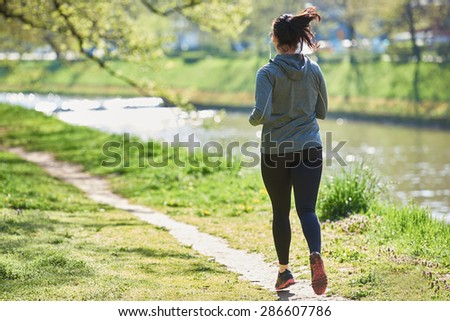 young woman jogging in city park at early morning - stock photo