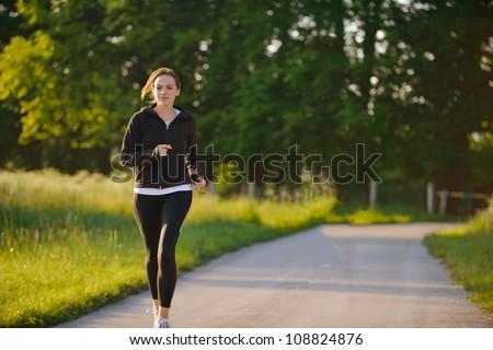 Young woman jogging in park at morning. Health and fitness. - stock photo