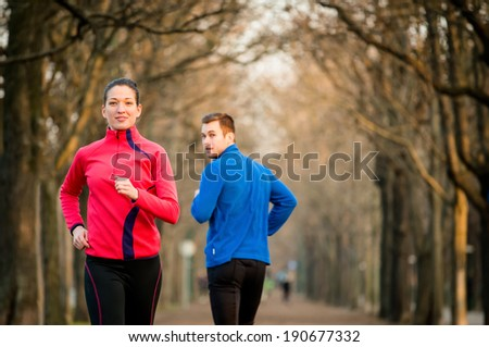 Young woman jogging in park, man running from opposite direction turns on her - stock photo
