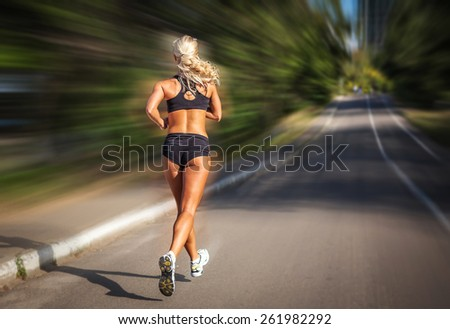 young woman jogging in the park in summer - stock photo
