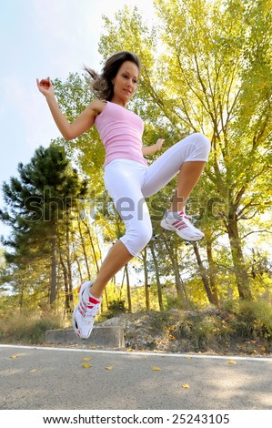 young woman jogging/jumping on a road