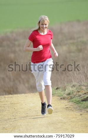 young woman jogging on a dirt road - stock photo
