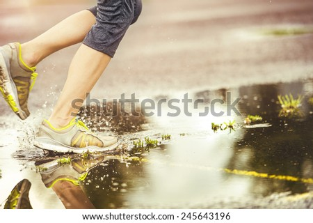 Young woman jogging on asphalt in rainy weather - stock photo