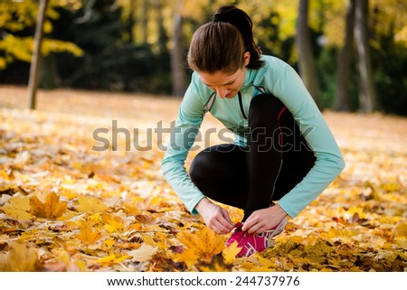 Young woman jogging tying shoelaces on jog in autumn nature - stock photo