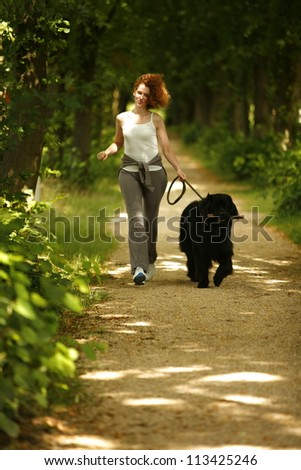 Young woman jogging with her dog in the park - stock photo
