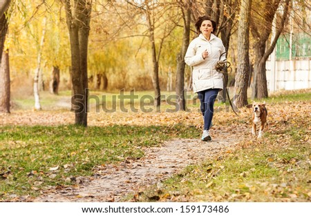 Young woman jogging with her pet in autumn park - stock photo