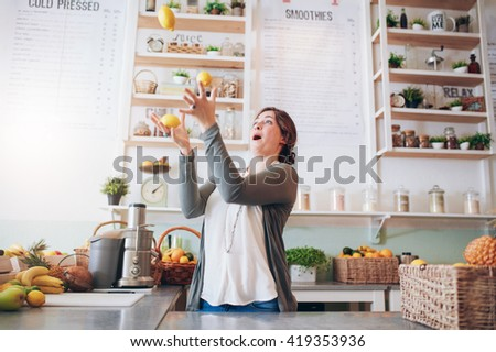 Young woman juggling with lemon at juice bar. Happy young female employee playing with fruits at juice bar. - stock photo