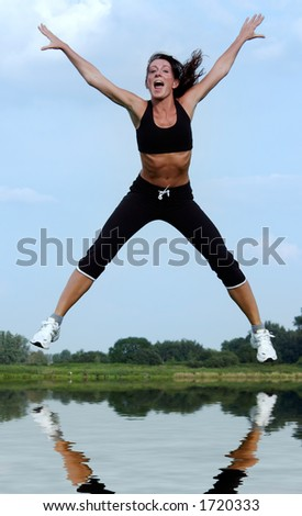 young woman jumping above water