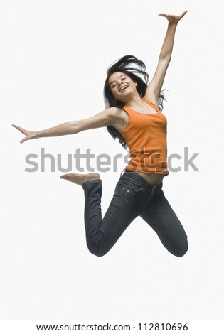 Young woman jumping against white background