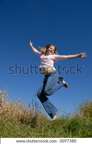 Young woman jumping happily in a field with blue sky in background - stock photo