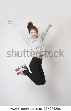 Young woman jumping high in happiness - studio shot. - stock photo