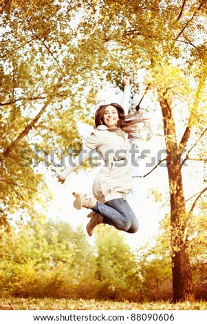 young woman jumping in autumn park