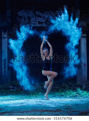 Young woman jumping in blue powder cloud on deserted factory grunge background - stock photo