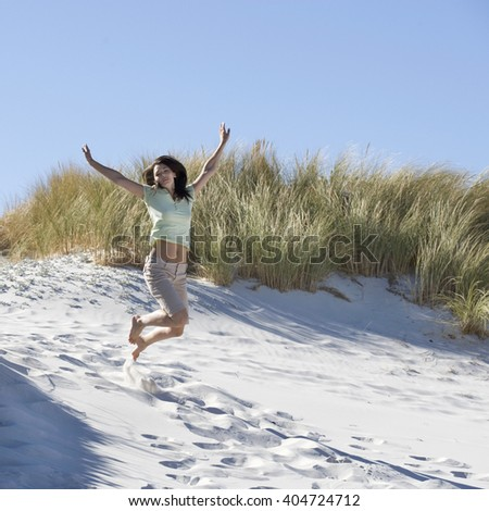 Young woman jumping in sand dunes - stock photo