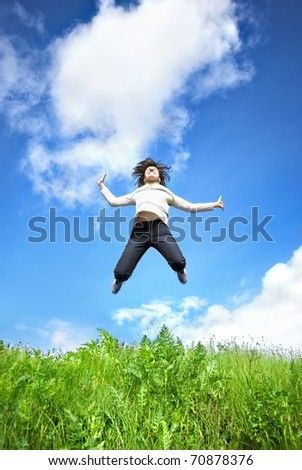 Young woman jumping into the field against the blue sky