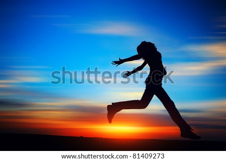 Young woman jumping on meadow on motion blurred sunset background.