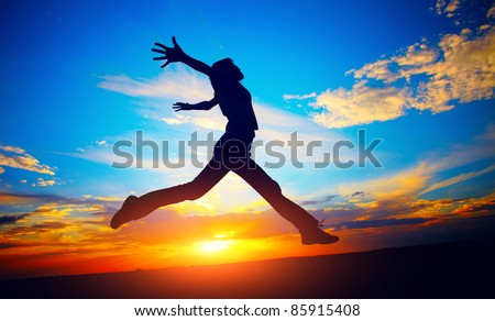 Young woman jumping on meadow on sunset sky background - stock photo