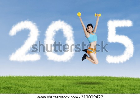 Young woman jumping on meadow while holding two dumbbells and forming number 2015
