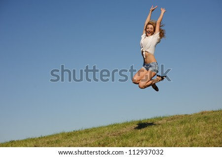 Young woman jumping on the green summer field - stock photo