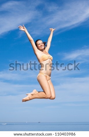 Young woman jumping outdoors. Girl hopping with arm raised on background of sky - stock photo