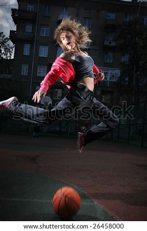 Young woman jumping over basketball ball - stock photo