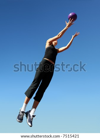 Young woman jumping to catch the ball - stock photo