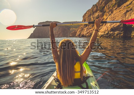 Young woman kayaking and holding oar over head - stock photo
